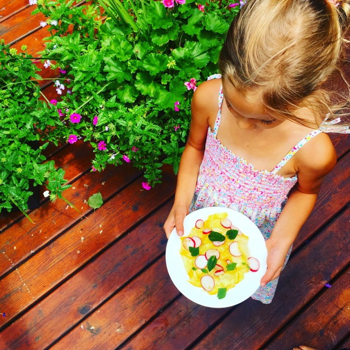 girl holding summer squash and radish salad with fresh mint